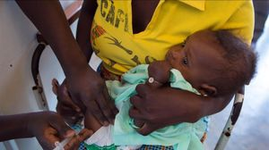 Un técnico sanitario vacuna a un bebé en Hindane (Mozambique).
