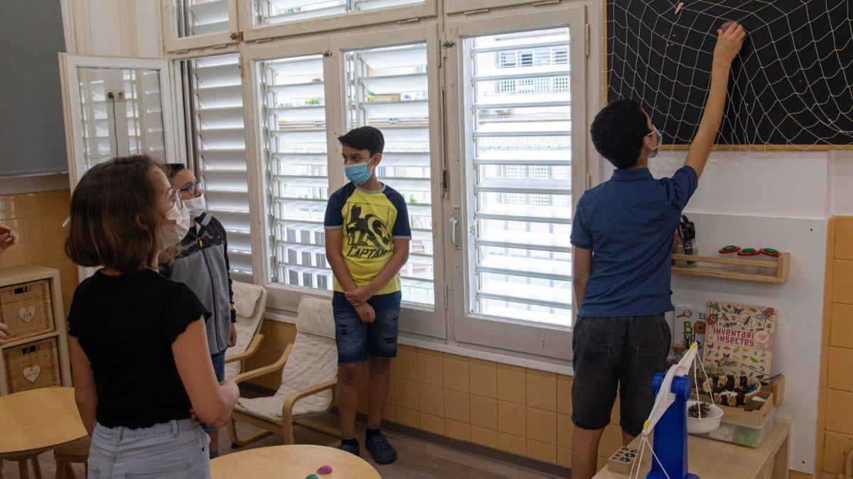 Aula con niños y profesora llevando mascarillas.