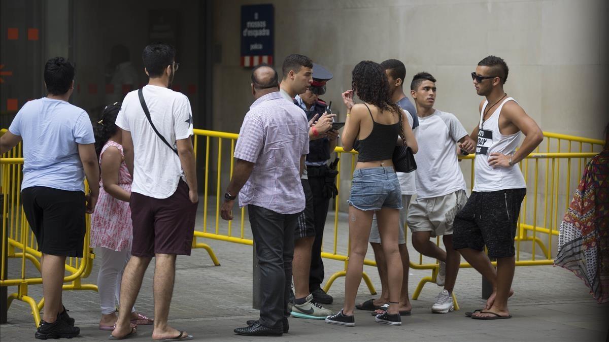 Una agente informa a los ciudadanos en la entrada de la comisaría de Ciutat Vella de Barcelona que hay tres horasde cola para denunciar un delito, el pasado jueves al mediodía.