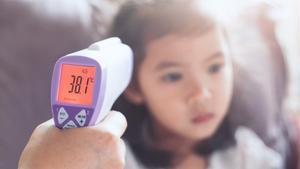 Una madre toma la temperatura a su hija con un termómetro de infrarrojos.