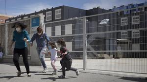 Un grupo de niños juegan en la puerta de una escuela del Poblenou, en mayo.