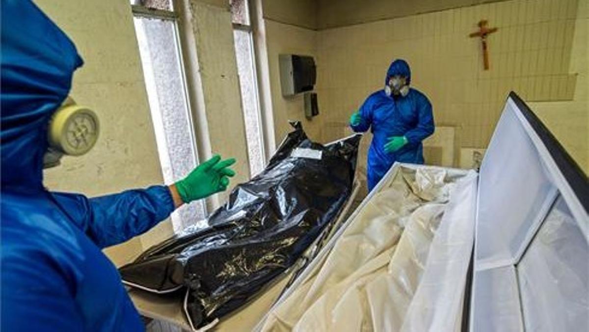 Trabajadores de una funeraria mexicana recogen el cadáver de un fallecido por covid-19 de un hospital en la Ciudad de México, el 1 de junio del año pasado.