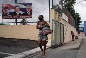 Una mujer pasa junto a un cartel con las fotografías de Fidel Casto, Raúl Castro y del actual presidente del país Miguel Diaz Cane, en La Habana.