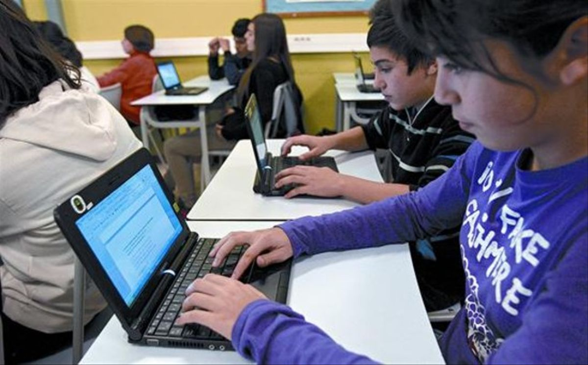 Alumnos de ESO del colegio Juan XXIII de L'Hospitalet de Llobregat, trabajando con los ordenadores en clase.