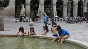 Un grupo de niños juegan en la fuente de la plaza Reial de Barcelona, el 9 de julio.
