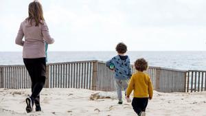 Madre con sus dos hijos en la playa.