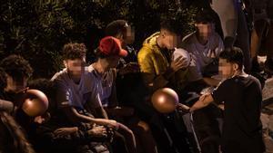 Varios jóvenes inhalan óxido nitroso con globos en el macrobotellón de la playa de Bogatell.