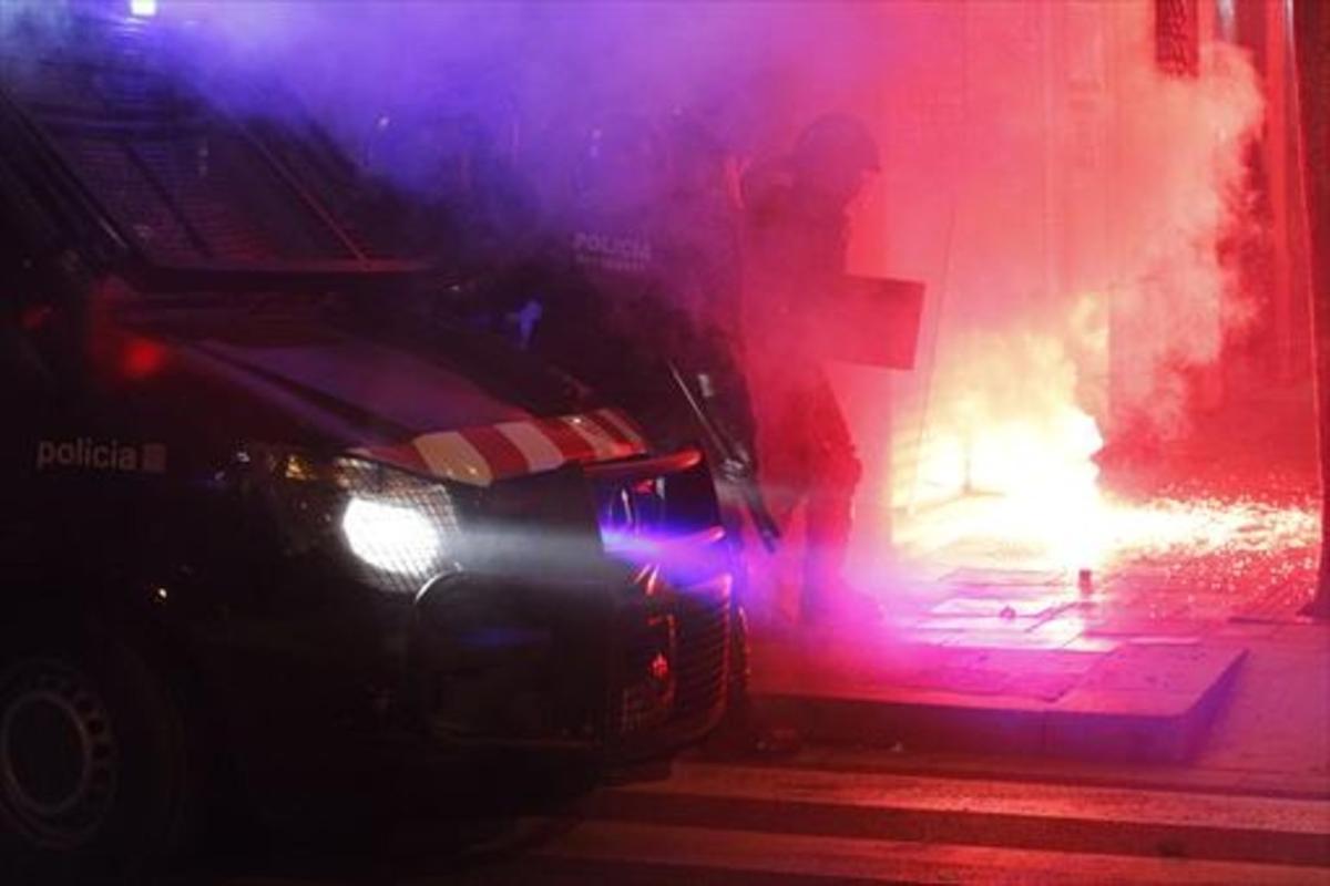 Varios mossos intentan sofocar uno de los incendios provocados en Gràcia.
