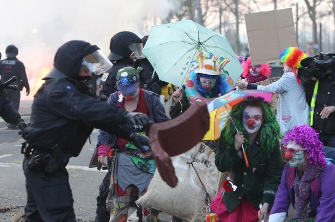 Manifestantes vestidos de payasos se encaran a varios agentes.