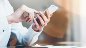 Una persona utilizando el teléfono móbil para llevar a cabo sus gestiones financieras.