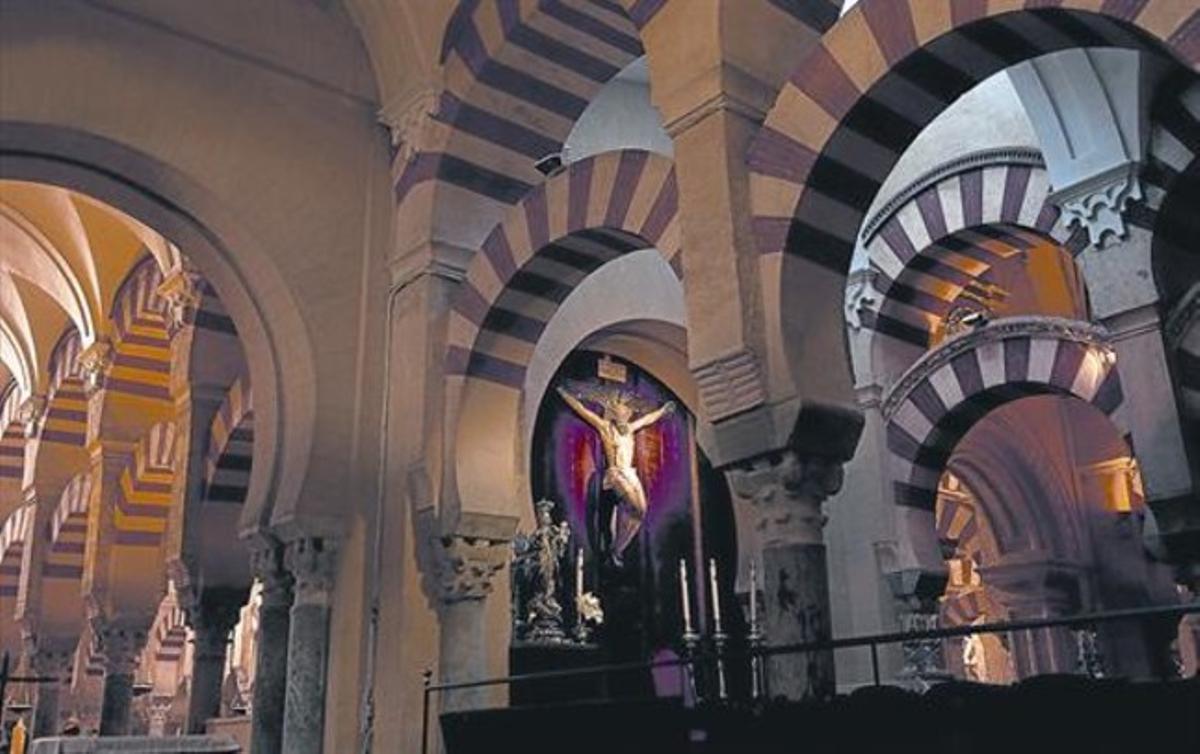 Interior de la mezquita-catedral de Córdoba, con un altar presidido por un gran crucifijo y una virgen de plata.