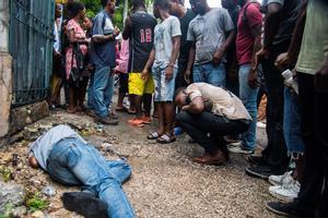 Personas observan a un hombre fallecido durante protestas para pedir la renuncia del presidente, Jovenel Moise.