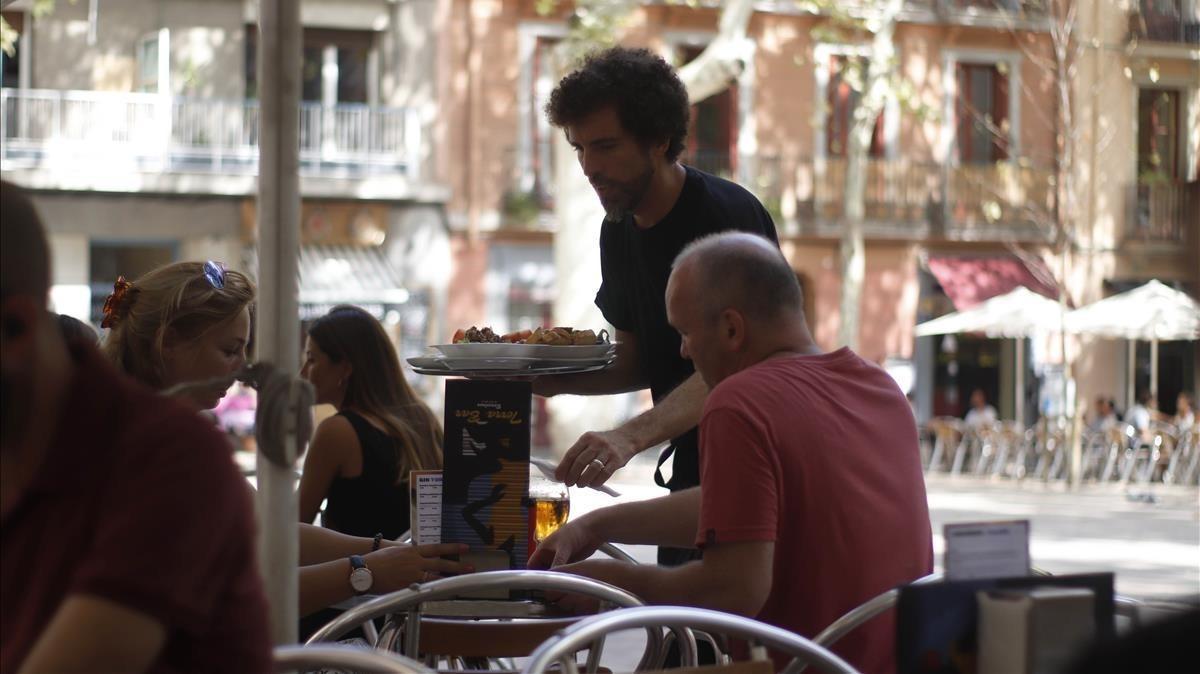 Un camarero atiende a unos clientes en Barcelona.