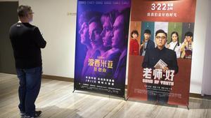 Un cliente de un cine chino observa un cartel de la película 'Bohemian Rhapsody' en Pekín.