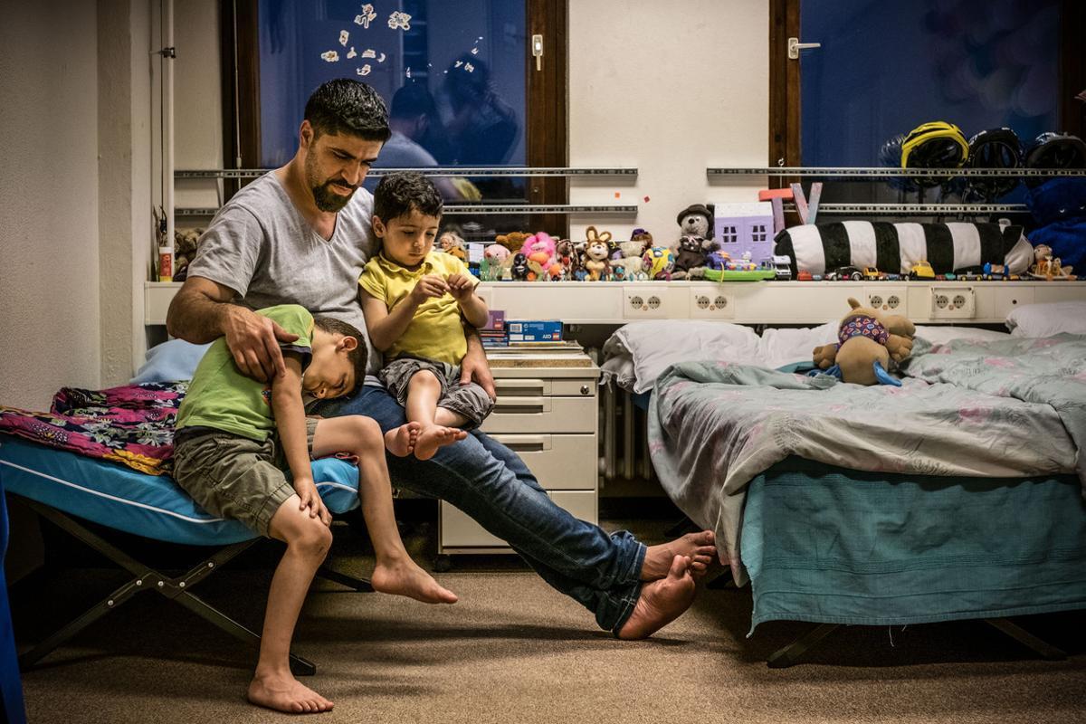 Un refugiado sirio explica cuentos a sus hijos antes de dormir, en un centro de acogidaen Prenzlauer Berg (Alemania).