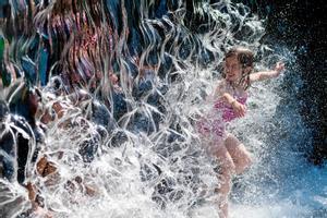 Una niña se refresca en una cascada de agua en un parque en Washington DC.