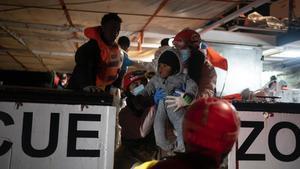 Miembros de la tripulación del 'Open Arms' ayudan a subir a bordo del barco a un bebé rescatado.