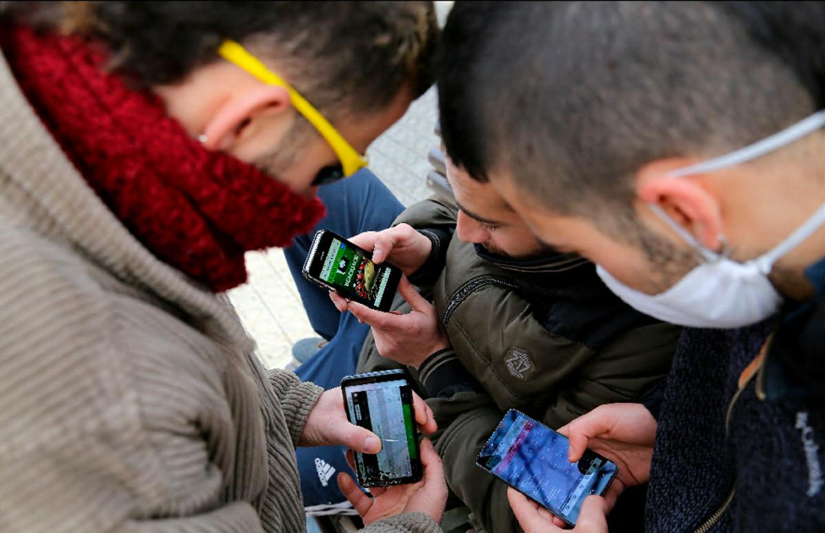 Varios jóvenes miran sus móviles