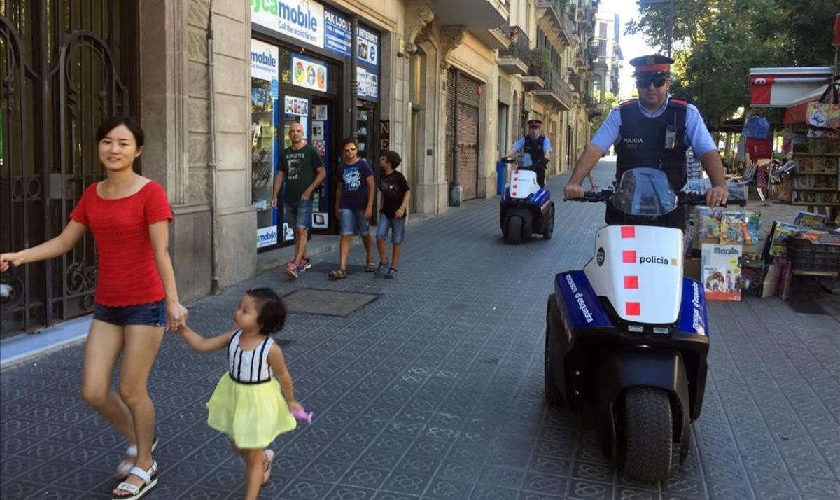 Una patrulla de los Mossos d'Esquadra con un 'Segway' por la calle de Consell de Cent.