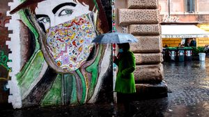 Una mujer pasa frente a un grafiti en el barrio de Trastevere de Roma.