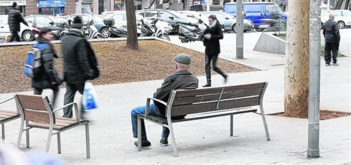 Un anciano sentado en un banco de la avenida de Roma.