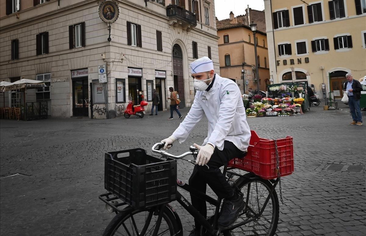 Un cocinero circula enbicicleta por una plaza desierta de Campo Dei Fiori.