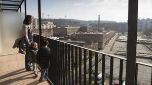 Los pequeños Otger y Guifré miran los terrenos de Can Batlló desdeel balcón de su nueva casa, junto a Ares, su madre,este sábado.