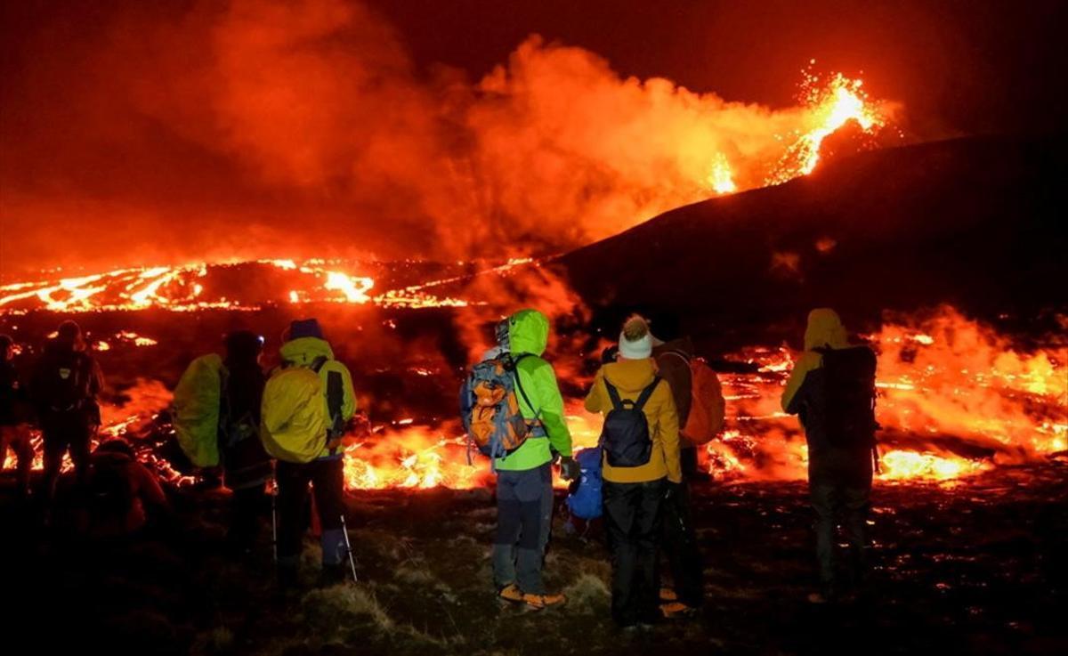 Erupción volcánica a unos 40 kilómetros de la capital de Islandia. En la foto, algunos visitantes contemplan el espectacular fenómeno.