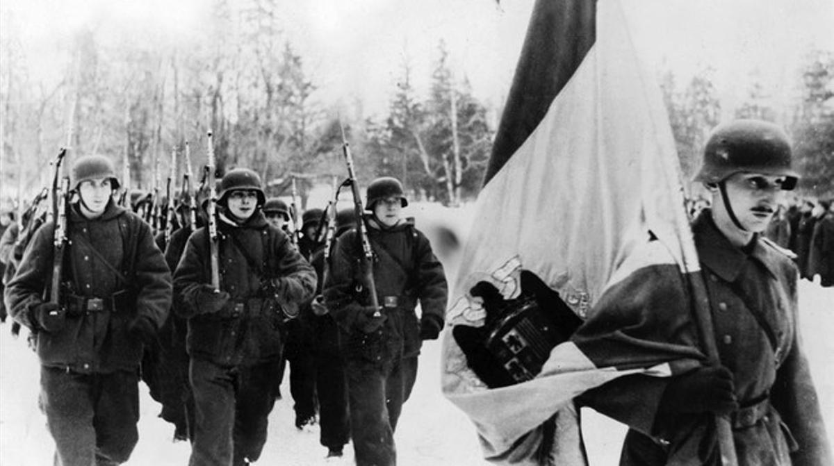 Integrantes de la División Azul, con el uniforme alemán de la 250 División de Infantería, desfila tras la bandera de la España de Franco camino de Leningrado.