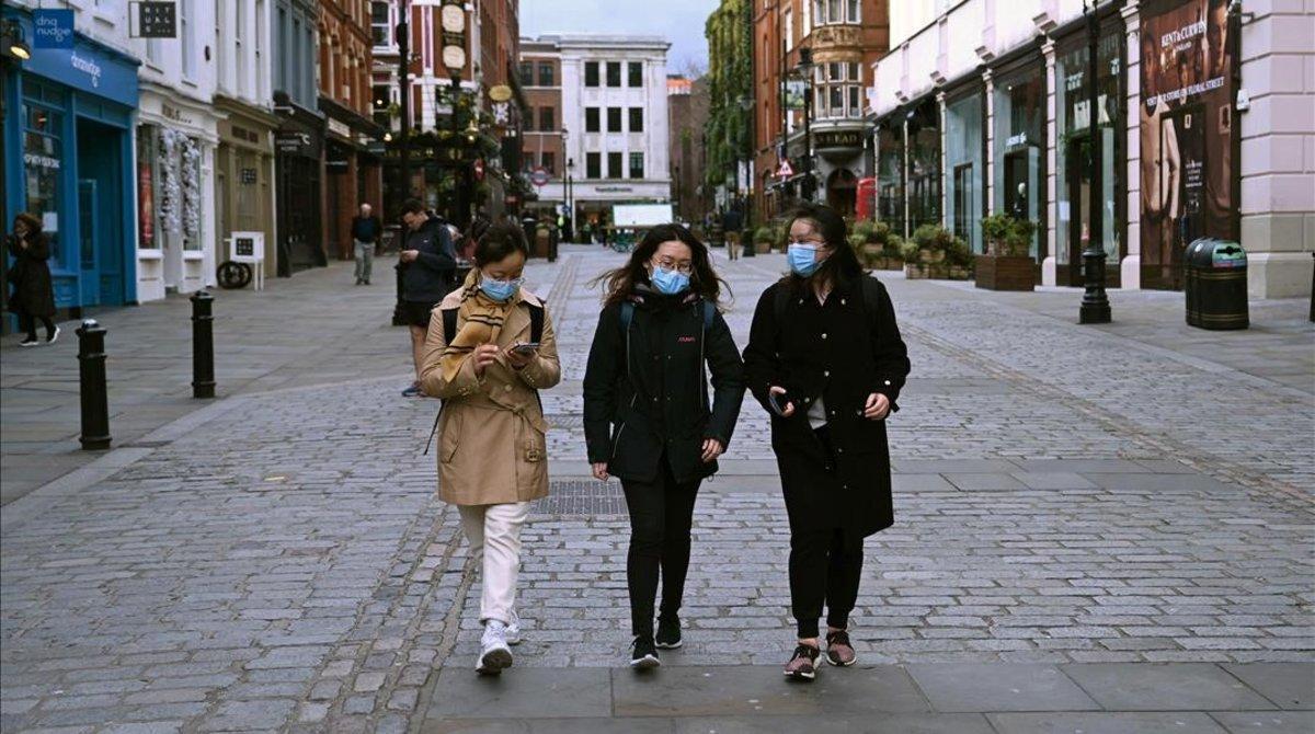 Personas con máscaras caminan en una tarde inusualmente tranquila en Covent Garden, en Londres.