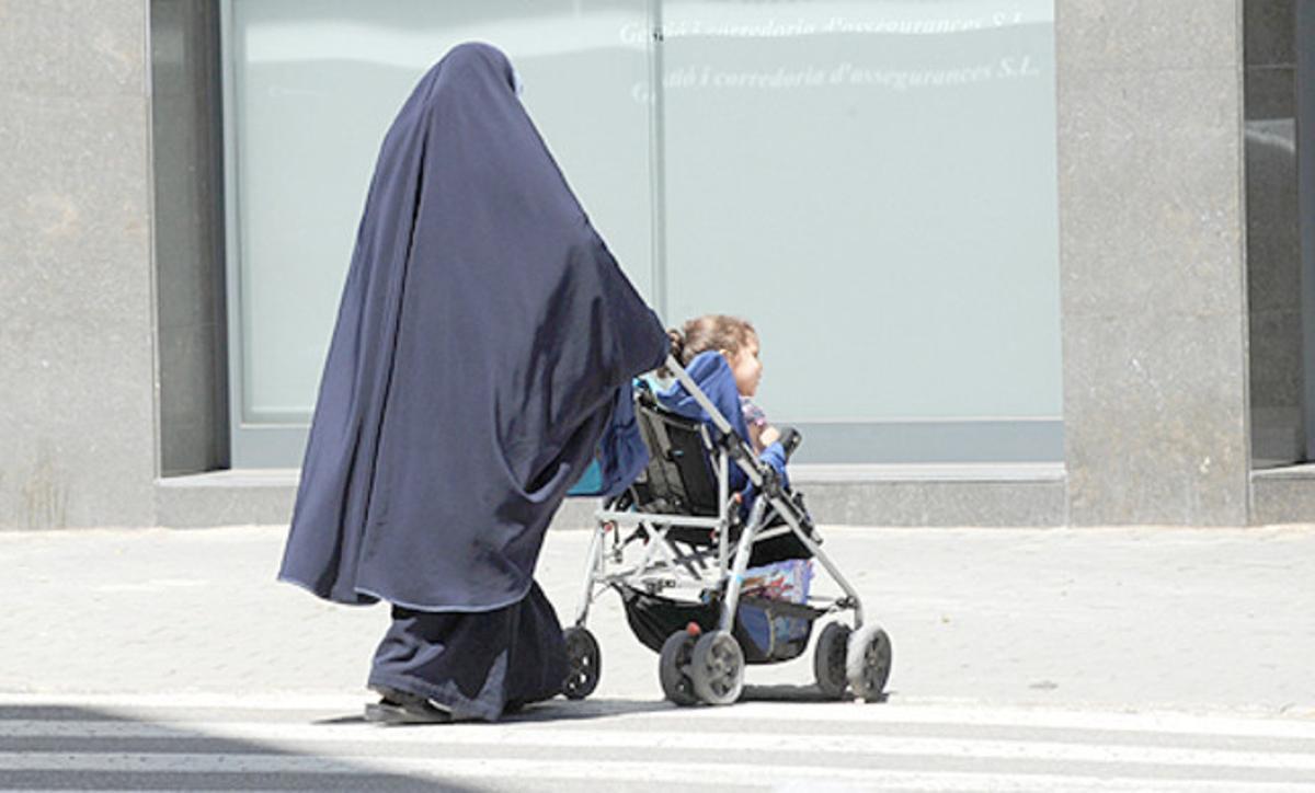 Una mujer con burka pasea con su hijo.