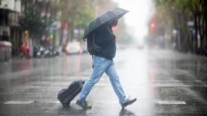 Alerta por lluvias en toda Catalunya. En la foto, un hombre cruza la calle de Aragó bajo la lluvia. En el vídeo, fuerte oleaje en las playas del Maresme.