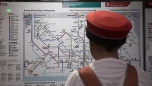 Un usuario mira un mapa del metro de Barcelona.