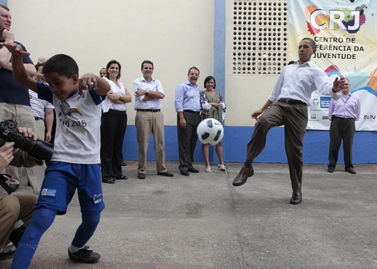 Barack Obama da unos toques a un balón de fútbol, este domingo, durante su visita a la favela Ciudad de Dios, en Río de Janeiro.
