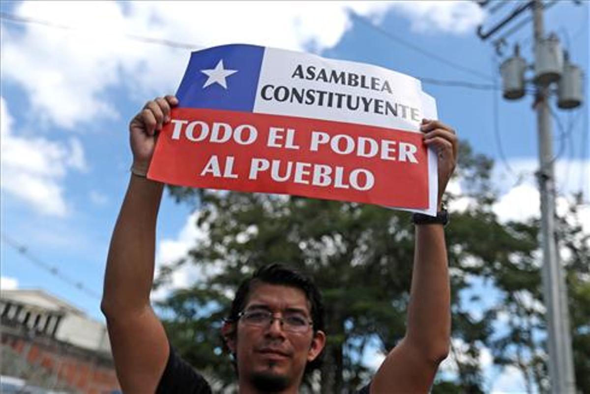 Un hombre se manifiesta en apoyo a las protestas chilenas frente a la Embajada de Chile en El Salvador.