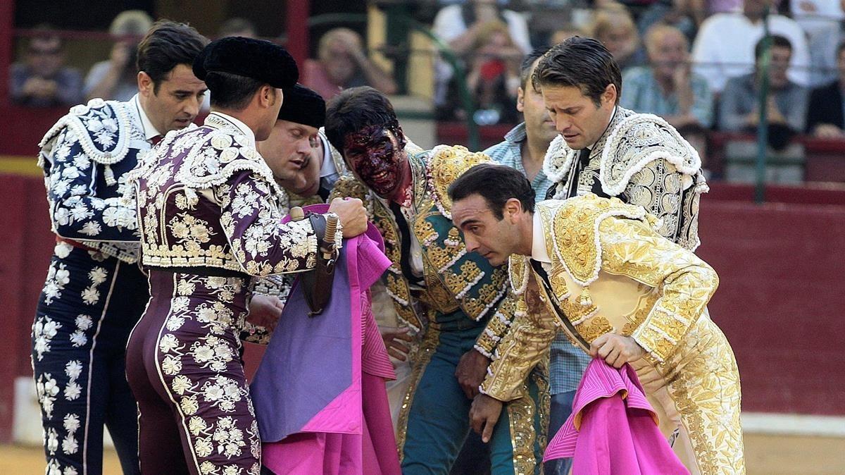 EL diestro, con la sangre del toro en la cara, es atendido tras la cogida.