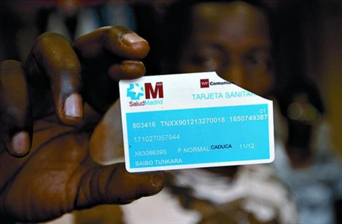 Un inmigrante muestra su tarjeta sanitaria inutilizada, en Torrejón de Ardoz (Madrid).