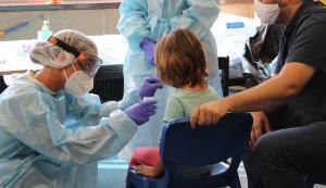 Una sanitaria le realiza un test PCR a una menor.