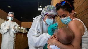 La escalada de contagios obliga a Aragón y a Murcia a endurecer las restricciones. En la foto, una sanitaria realiza un test PCR a un niño en un espacio habilitado fuera de un Centro de Salud de la ciudad de Zaragoza, el pasado 1 de julio.