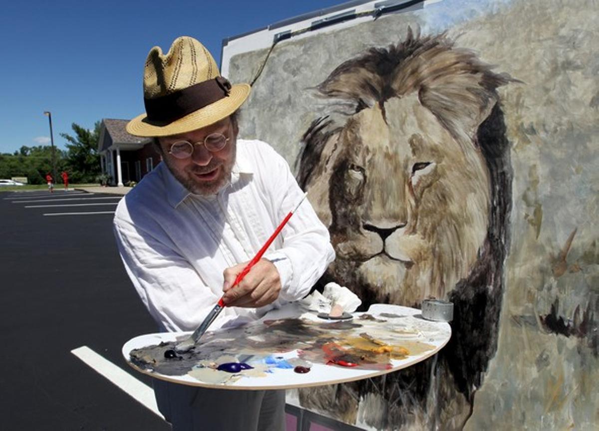 El artista californiano Mark Balma pinta a Cecil ante la clínica del dentista Walter James Palmer, este miércoles.