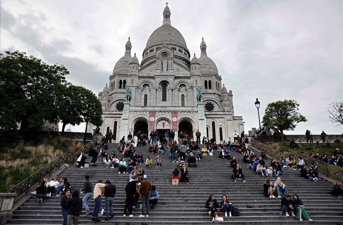 La gente toma bebidas frente al Sacre Coeur.
