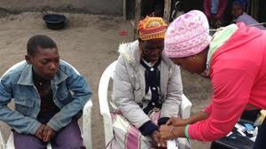 Gerlito (a la izquierda), el joven enfermo de malaria, mira como le hacen la prueba a su madre.