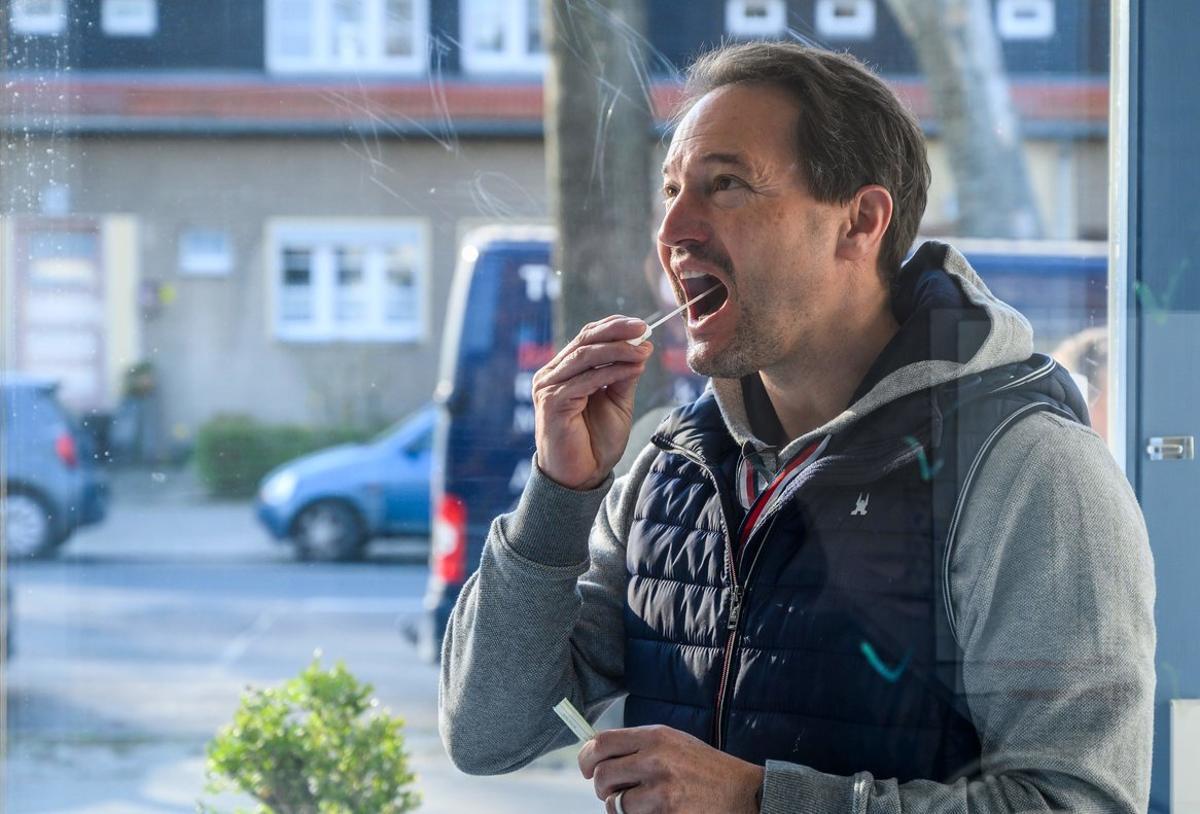 Un hombre se coge una muestra de saliva para hacerse el test de coronavirus.