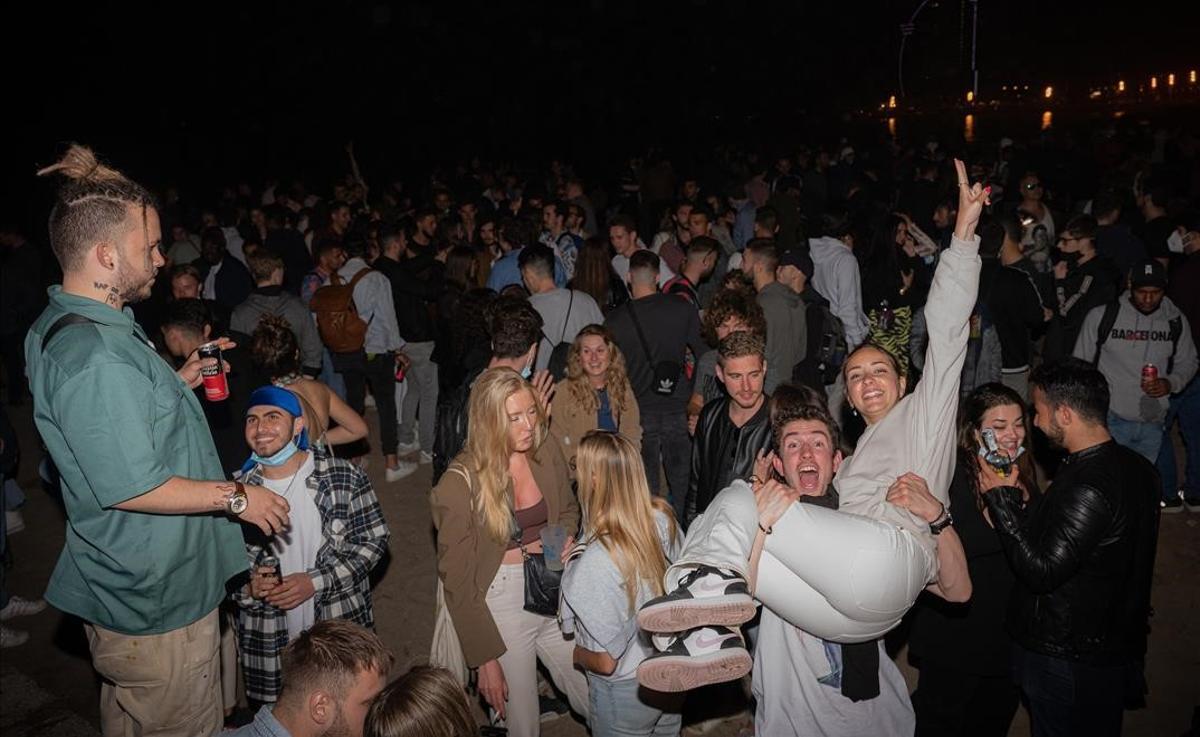Jóvenes de fiesta en la Barceloneta, tras el final del toque de queda.