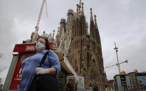 Una mujer con mascarilla para protegerse del coronavirus frente a la Sagrada Família.