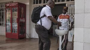 Un hombre se lava las manos antes de entrar en un supermercado en Gisenyi, en Ruanda, para evitar posibles contagios de ébola.