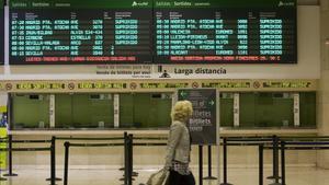 Una mujer pasa delante de un panel informativo con trenes suprimidos en Sants.