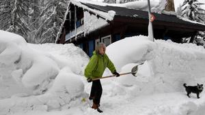 Una mujer aparta la nieve en Val D'Isere, en los Alpes franceses.