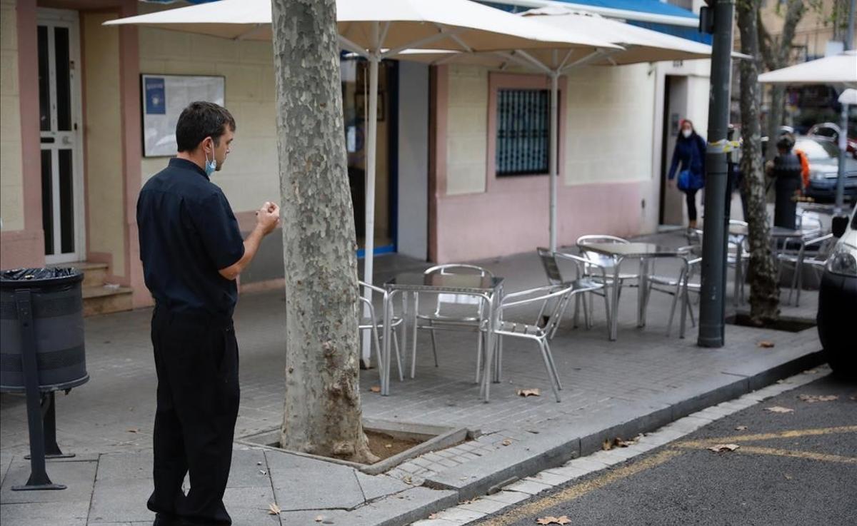 El mercado laboral pierde 137.500 empleos en mitad de la tercera ola. En la foto, un camarero observa la terraza de su restaurante, vacía, en un local de la rambla del Poblenou, en Barcelona.