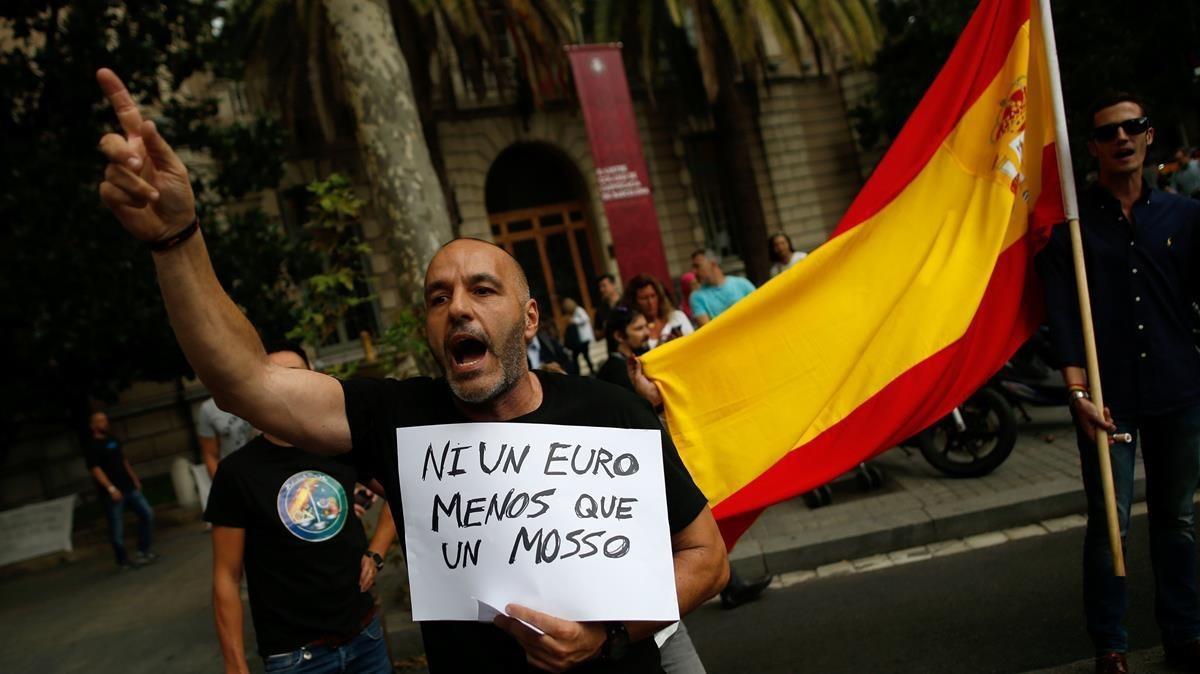 Un manifestantepolicial reclama equiparación salarial respecto a los Mossos,frente a la Delegacióndel Gobierno en Barcelona.